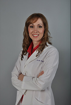 Dr. Dodig wearing her white coat and red collard shirt smiling