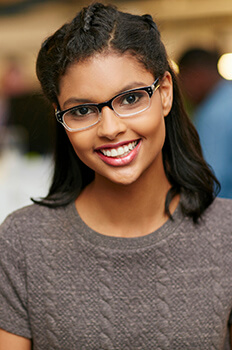 Young woman wearing glasses and brown sweater