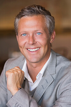 man with a grey suit and blue eyes smiling
