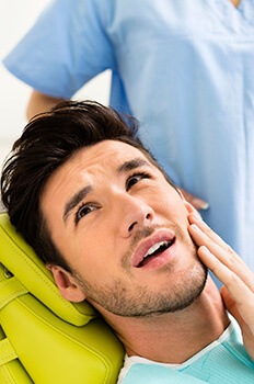 man in dental pain holding cheek