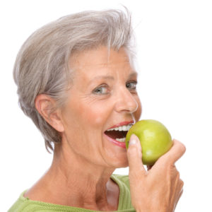 older woman preparing to bite apple