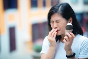 person with dental sensitivity caused by gum disease in Houston eating ice cream
